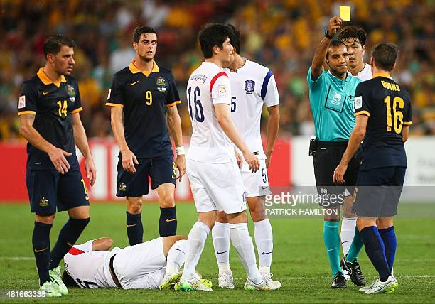 Referee Nawaf Shukralla issues a yellow card to Nathan Burns during the first round Asian Cup football match between South Korea and Australia at the...