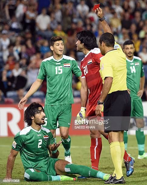 Referee Nawaf Shukralla of Bahrain gives a red card to Iraq's Ahmed Ibrahim as Iraq's goalkeeper Mohammed Hameed looks on during the thirdplace...