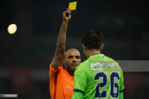 Referee Nawaf Shukralla shows a yellow card to Hong JeongHo of Jeonbuk Hyundai Motors during the AFC Champions League round of 16 first leg match...