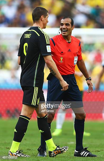Referee Nawaf Shukralla speaks to Fernando Torres of Spain as he walks to the sideline to remove his torn jersey during the 2014 FIFA World Cup...