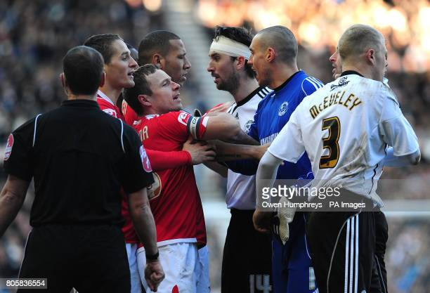 Referee Neil Swarbrick looks on as Nottingham Forest's Paul McKenna is held back by Derby County goalkeeper Stephen Bywater after clashing with Derby...