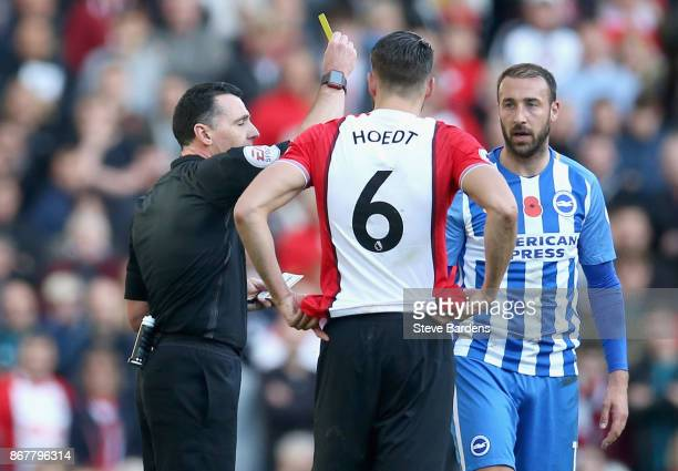 Referee Neil Swarbrick shows a yellow card to Glenn Murray of Brighton and Hove Albion as Wesley Hoedt of Southampton looks on during the Premier...