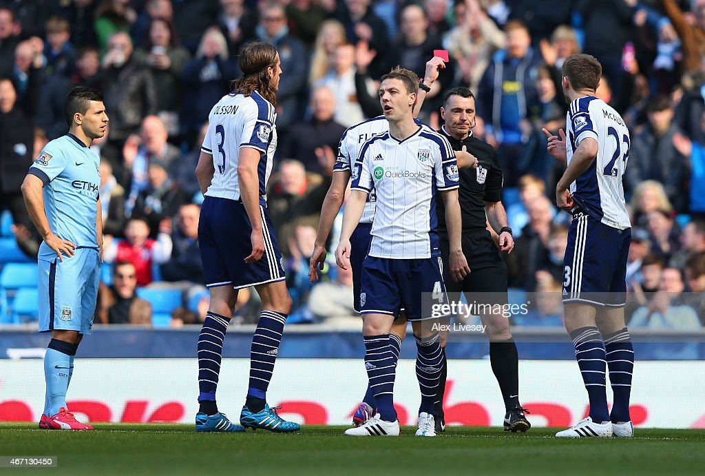 Referee Neil Swarbrick shows Gareth McAuley of West Brom (R) a red card during the Barclays Premier League match between Manchester City and West Bromwich Albion at Etihad Stadium on March 21, 2015 in Manchester, England.