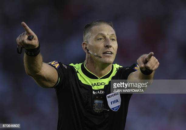 Referee Nestor Pitana gestures during the Argentine derby match between River Plate and Boca Juniors in the Superliga first division tournament at...