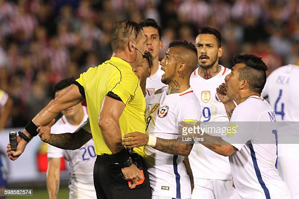 Referee Nestor Pitana shows a red card to Gary Medel of Chile as Eduardo Vargas and Arturo Vidal of Chile shout at him during a match between...