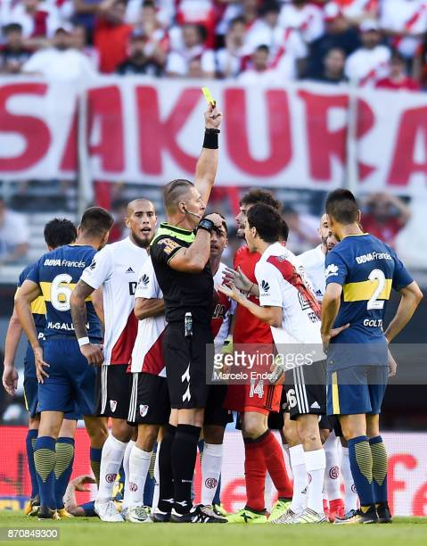 Referee Nestor Pitana shows a yellow card to Germán Lux of River Plate during a match between River Plate and Boca Juniors as part of the Superliga...