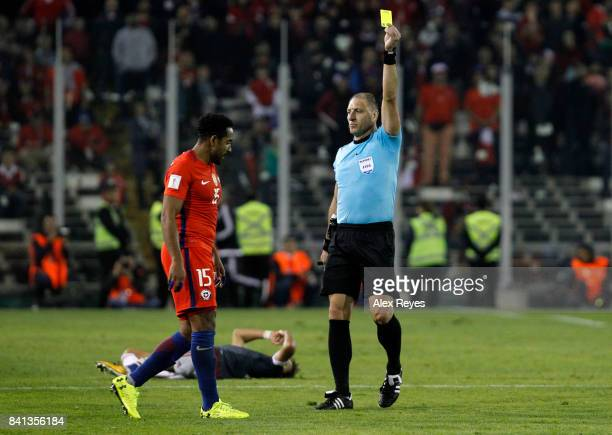 Referee Nestor Pitana shows a yellow card to Jean Beausejour of Chile during a match between Chile and Paraguay as part of FIFA 2018 World Cup...