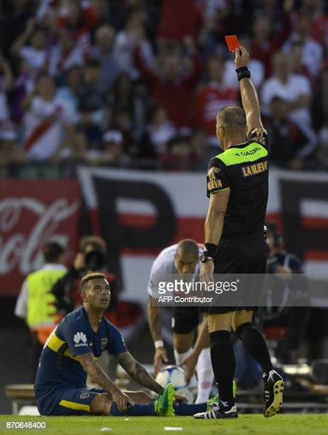 Referee Nestor Pitana shows the red card to Boca Juniors' Colombian midfielder Edwin Cardona during the Argentine derby match against River Plate in...
