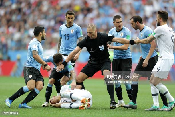 Referee Nestor Pitana stops Diego Godin, Nahitan Nandez and Luis Suarez of Uruguay from arguing with Kylian Mbappe of France during the 2018 FIFA...