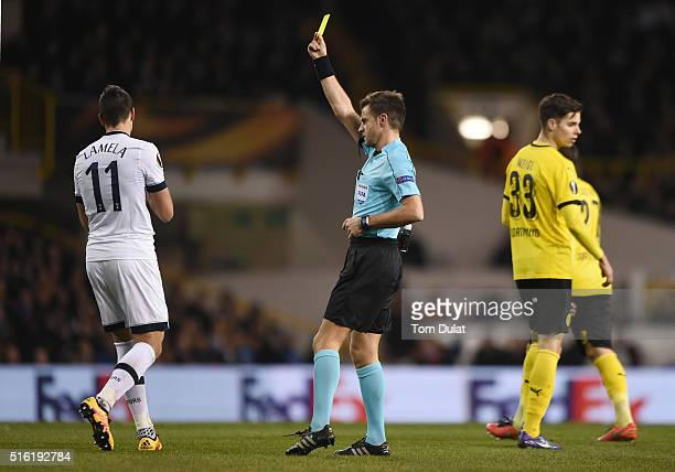 Referee Nicola Rizzoli shows a yellow card to Erik Lamela of Tottenham Hotspur during the UEFA Europa League round of 16 second leg match between...