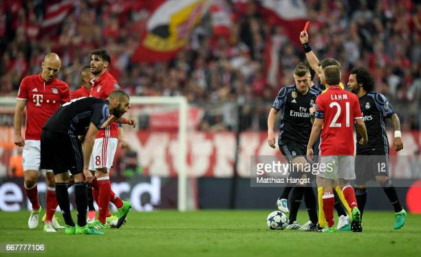 Referee Nicola Rizzoli shows the yellow red card to Javi Martinez of Muenchen during the UEFA Champions League Quarter Final first leg match between...