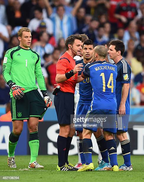 Referee Nicola Rizzoli speaks to Sergio Aguero Javier Mascherano and Lionel Messi of Argentina after a collision between goalkeeper Manuel Neuer of...