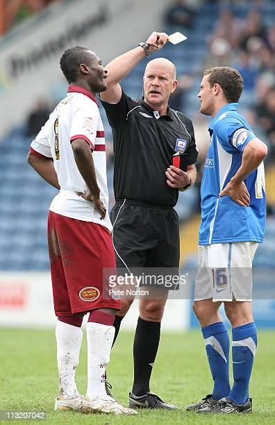 Referee Nigel Miller shows a yellow card to Abdul Osman of Northampton Town as James Wallace of Stockport County looks on during the npower League...