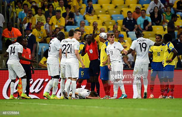 Referee Noumandiez Doue calls a stretcher as Lucas Digne of France lies injured after a challenge by Antonio Valencia of Ecuador during the 2014 FIFA...