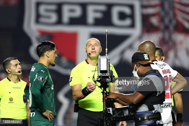 Referee Néstor Pitana performs the coin toss with team captains Gustavo Gómez of Palmeiras and Miranda of Sao Paulo before a quarter final first leg...