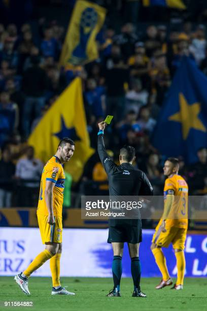 Referee Oscar Mejia gives a yellow card to AndrePierre Gignac of Tigres during the 4th round match between Tigres UANL and Pachuca as part of the...