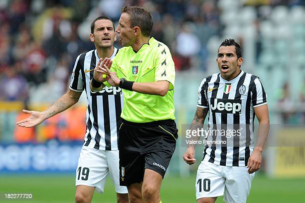 Referee Paolo Silvio Mazzoleni discutes with Leonardo Bonucci and Carlos Tevez of Juventus during the Serie A match between Torino FC and Juventus at...