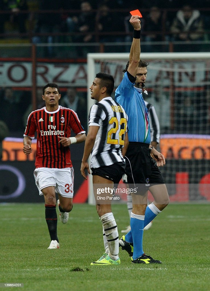 Referee Paolo Tagliavento (R) shows the red card to Arturo Vidal of Juventus during the Serie A match between AC Milan and Juventus FC at Stadio Giuseppe Meazza on February 25, 2012 in Milan, Italy.