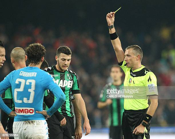 referee Paolo Valeri gives a yellow card to Sassuolo's midfielder from Italy Luca Mazzitelli during the Italian Serie A football match SSC Napoli vs...