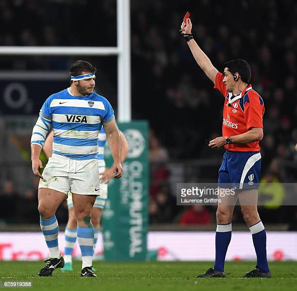 Referee Pascal Gauzere of France shows Enrique Pieretto of Argentina a red card during the Old Mutual Wealth Series match between England and...