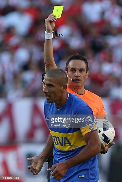 Referee Patricio Loustau issues a yellow card to Daniel Diaz of Boca Juniors during a match between River Plate and Boca Juniors as part of sixth...