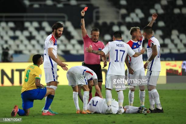 Referee Patricio Loustau shows a red card to Gabriel Jesus of Brazil as Eugenio Mena of Chile lies in the pitch injured during a quarterfinal match...