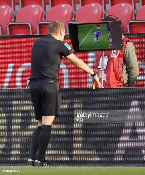 Referee Patrick Ittrich checks a penalty situation on the VAR screen during the Bundesliga match between 1. FSV Mainz 05 and FC Schalke 04 at Opel...