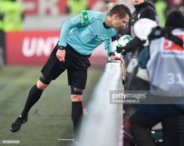 Referee Patrick Ittrich checks a TV control screen to take a decision during the German first division Bundesliga football match between VfB...