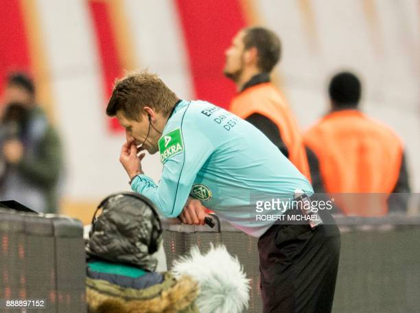Referee Patrick Ittrich checks the video assistant referee during the German first division Bundesliga football match between RB Leipzig and Mainz 05...
