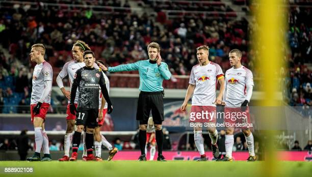 Referee Patrick Ittrich gestures to show he was in contact with the video assistant referee during the Bundesliga match between RB Leipzig and 1 FSV...