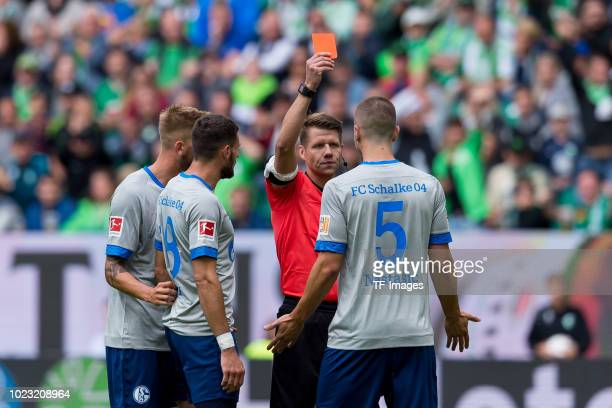 Referee Patrick Ittrich shows a red card to Matija Nastasic of FC Schalke during the Bundesliga match between VfL Wolfsburg and FC Schalke 04 at...