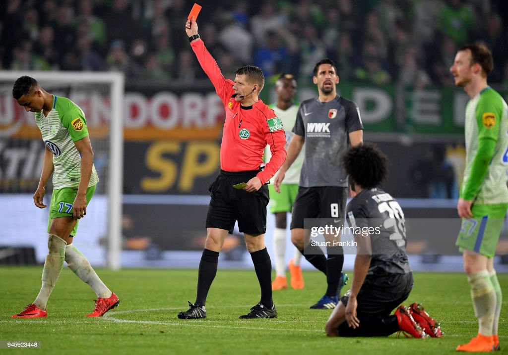 Referee Patrick Ittrich shows the red card to Felix Uduokha of Wolfsburg during the Bundesliga match between VfL Wolfsburg and FC Augsburg at Volkswagen Arena on April 13, 2018 in Wolfsburg, Germany.