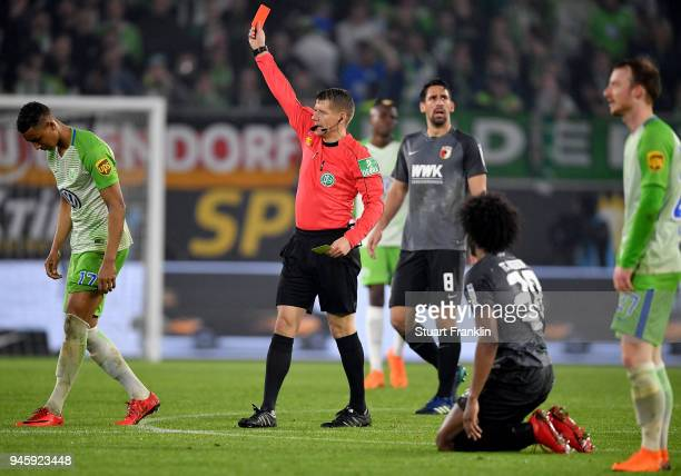 Referee Patrick Ittrich shows the red card to Felix Uduokha of Wolfsburg during the Bundesliga match between VfL Wolfsburg and FC Augsburg at...