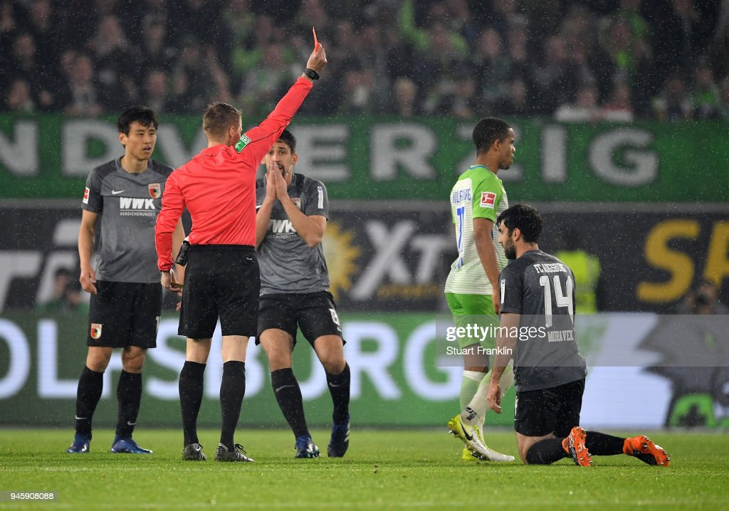 Referee Patrick Ittrich shows the red card to Jan Moravek of Augsburg during the Bundesliga match between VfL Wolfsburg and FC Augsburg at Volkswagen Arena on April 13, 2018 in Wolfsburg, Germany.