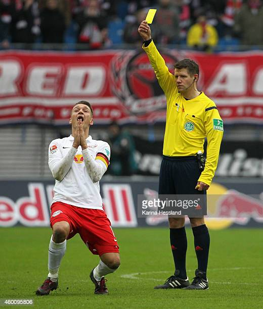 Referee Patrick Ittrich shows the yellow card to Daniel Frahn of Leipzig during the Second Bundesliga match between RasenBallsport Leipzig and FC...
