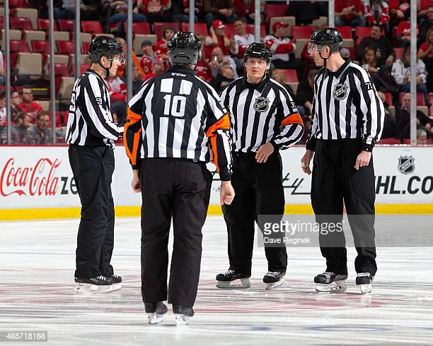 Referee Paul Devorski linesman Derek Amell and linesman Steve Barton gather around the first Russian referee Evgeny Romasko during his first NHL game...