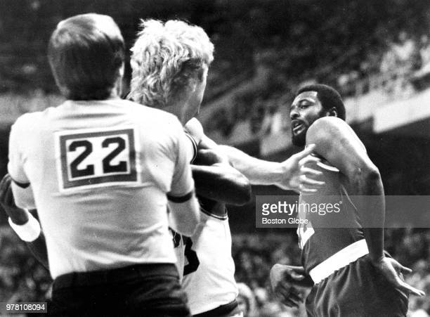 Referee Paul Mihalak and Boston Celtics' Gerald Henderson pull Larry Bird away from the Rockets' Joe Bryant in the first quarter The Boston Celtics...