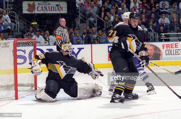 Referee Paul Stewart looks on as Tom Barrasso and Jiri Slegr of the Pittsburgh Penguins skate against Derek King of the Toronto Maple Leafs during...