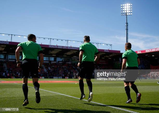 Referee Paul Tierney and his assistants go through their pre match warm up during the Premier League match between AFC Bournemouth and Everton FC at...