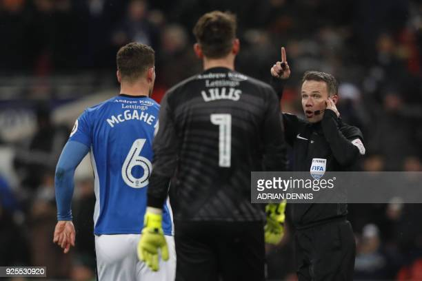 Referee Paul Tierney listens to VAR decision on Tottenham Hotspur's Argentinian midfielder Erik Lamela's goal which is disallowed during the English...