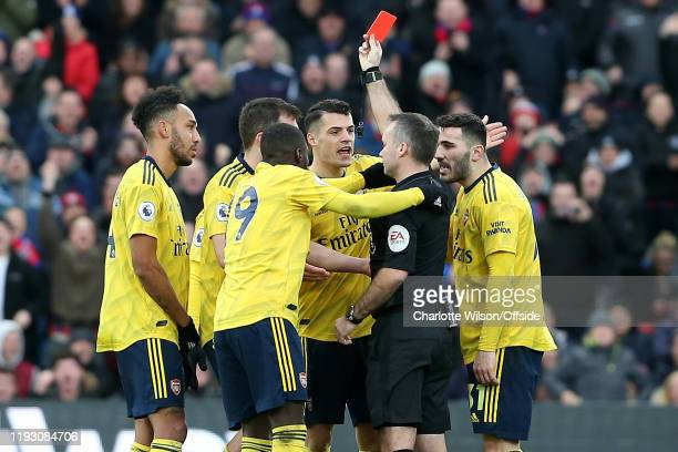 Referee Paul Tierney shows PierreEmerick Aubameyang of Arsenal a red card after VAR converts the original yellow card during the Premier League match...
