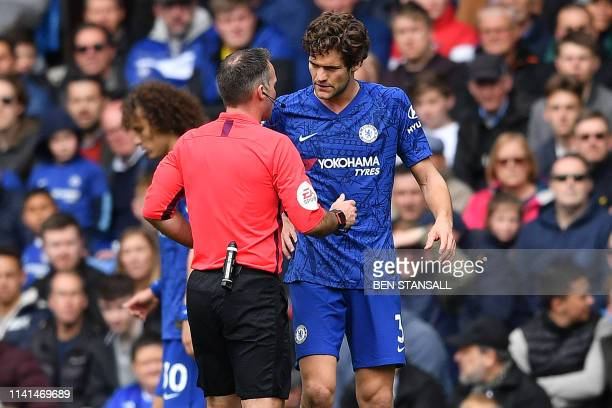 Referee Paul Tierney talks with Chelsea's Spanish defender Marcos Alonso after his challenge on Watford's English midfielder Will Hughes during the...