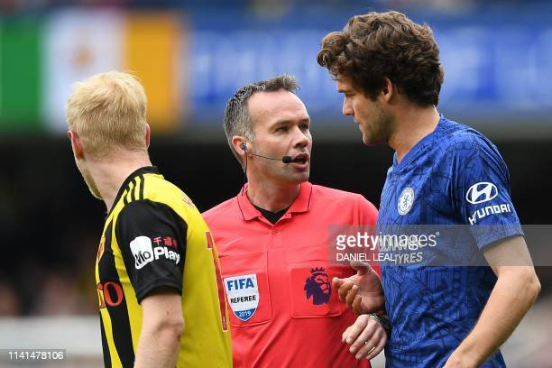 Referee Paul Tierney talks with Watford's English midfielder Will Hughes and Chelsea's Spanish defender Marcos Alonso during the English Premier...