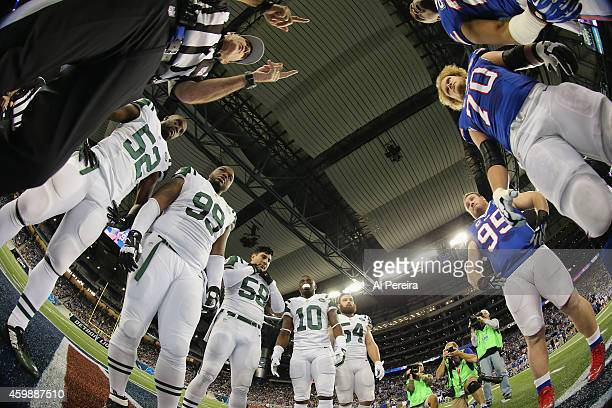 Referee Pete Morelli performs the coin toss with Captains of the Buffalo Bills and the New York Jets at Ford Field on November 24 2014 in Detroit...