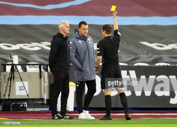 Referee Peter Bankes shows the yellow card to John Terry and a member of the West Ham backroom staff during the Premier League match between West Ham...