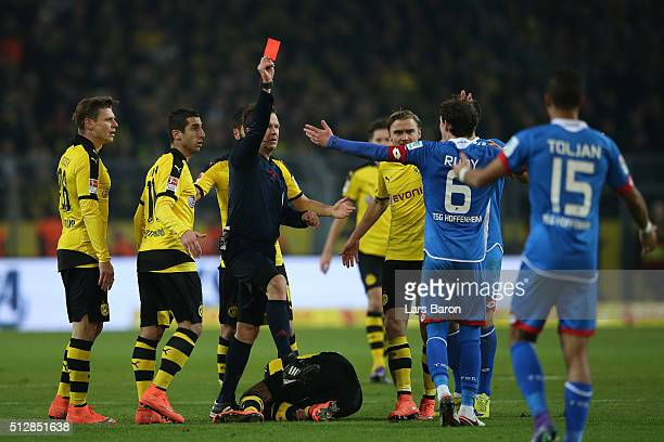 Referee Peter Sippel shoes the red card to Sebastian Rudy of 1899 Hoffenheim for a challenge on PierreEmerick Aubameyang of Borussia Dortmund during...