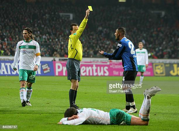 Referee Peter Sippel shows a yellow card to Ashkan Dejagah of Wolfsburg during the Bundesliga match between Werder Bremen and VfL Wolfsburg at the...