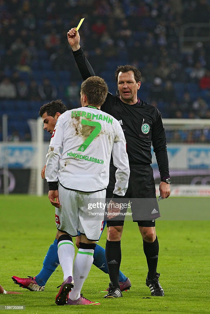 Referee Peter Sippel (R) shows the yellow card to Patrick Herrmann (L) of Moenchengladbach during the Bundesliga match between TSG 1899 Hoffenheim and VfL Borussia Moenchengladbach at Rhein-Neckar-Arena on January 19, 2013 in Sinsheim, Germany.