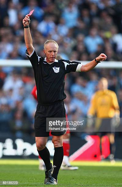 Referee Peter Walton shows a red card to Pablo Zabaleta of Manchester City during the Barclays Premier League match between Manchester City and...