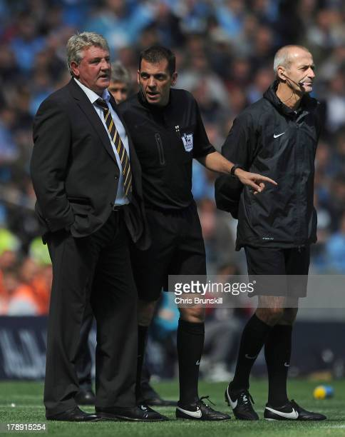 Referee Phil Dowd makes a point to Hull City manager Steve Bruce during the Barclays Premier League match between Manchester City and Hull City at...